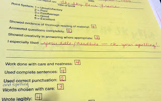 A book report evaluation form showing low scores in red ink and reminders to check spelling/grammar