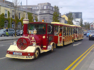 """Train"" style bus, using single-story open sided carriages pulled by an engine - but running on the road, not on train tracks.   Photographed at the north end of Eyre Square in Galway city, Ireland."