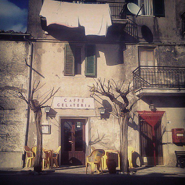 Italian signs, red fly curtains and a washing line in front of the local coffee bar in Petricci