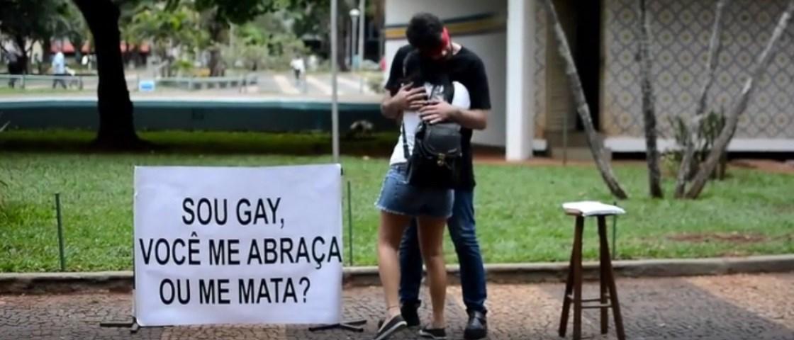 """Descrição: Um print de um vídeo que mostra um garoto vendado em uma rua sendo abraçado por uma mulher com a placa ao lado """"sou gay você me mata ou me abraça?"""""""
