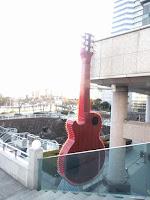 公園の奥の階段右下に赤い巨大ギターの背が見える
