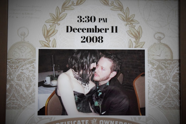 A close up picture of the framed certificate, a lady and man looking into each others eyes pictures on the certificate.