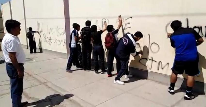 EJEMPLAR: Escolares ensucian pared de colegio y director los obliga a limpiarlas como correctivo