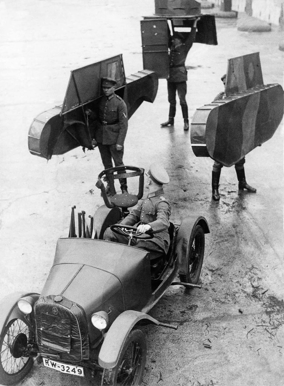 German soldiers carry the shell of a dummy tank to be attached to a car. 1931.