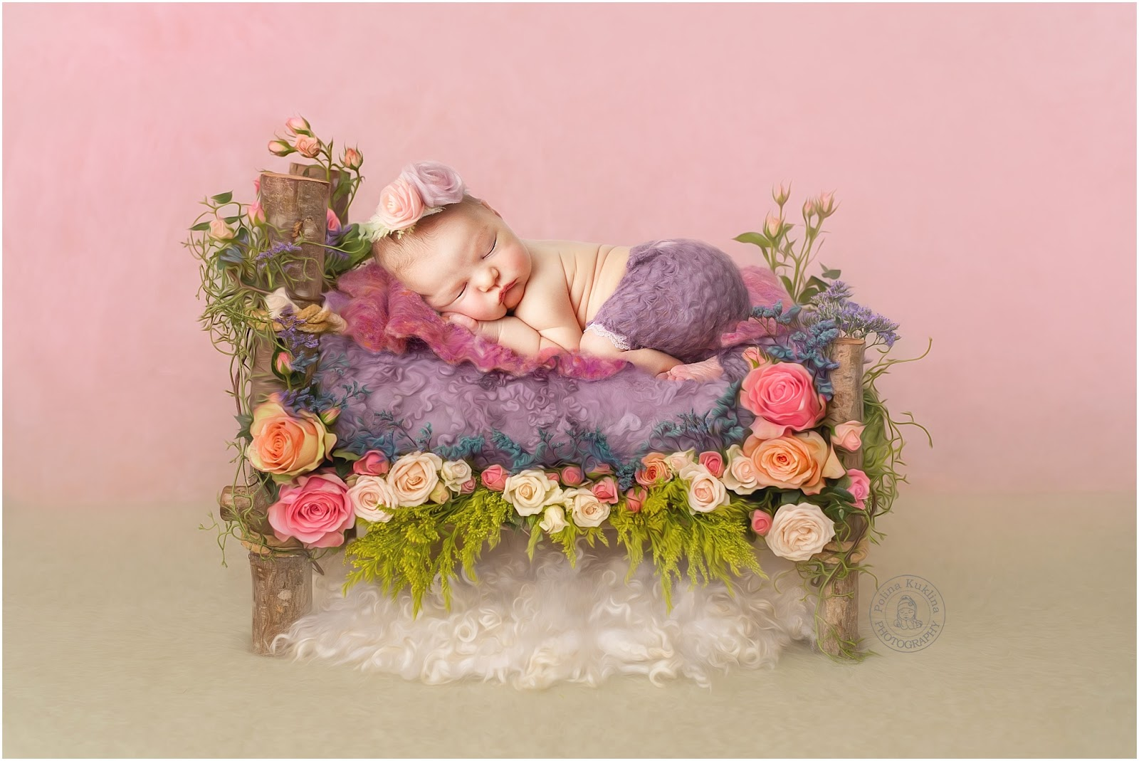 Newborn photo of a baby in a purple diaper with a flower headband on top of