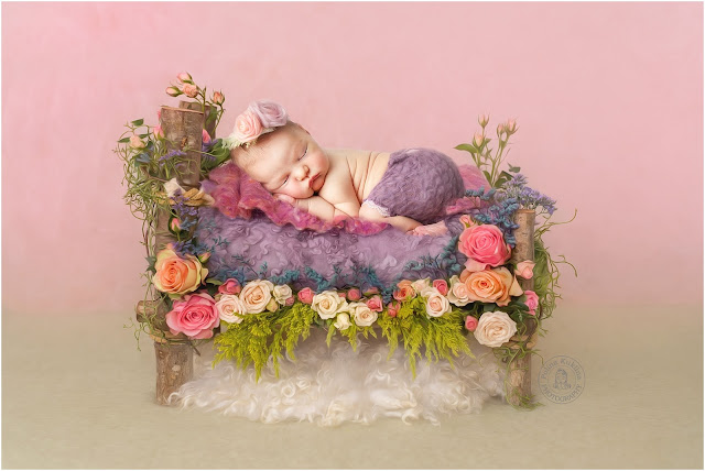 Newborn photo of a baby in a purple diaper with a flower headband on top of a wooden bed with flowers