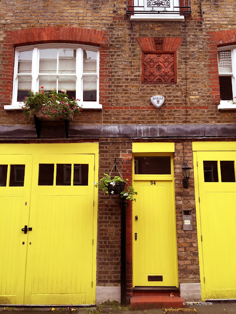 Three bright yellow wooden doors of a red brick house.