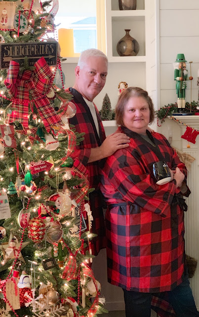 Decorated Christmas tree with a man and woman standing side by side in matching buffalo plaid pajamas