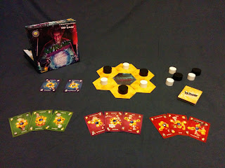 The game components. The box, with its cover art of a stereotypical mad scientist holding a large glowing sphere that contains the schematic image of an atom (the circle representing the nucleus and three oval orbits of the electrons around it), sits next to the tokens, tiles, and cards. In the centre is the main playing area: six yellow hexagonal tokens surrounding a blue hexagonal token with the 'Wrong Chemistry' title on it. The yellow tiles each have a large round wooden token on them, alternating black and white. A few extra tokens sit nearby, with the draw pile of the card deck next to them. On the other side of the tiles are two blue cards, the 'Restartium' and 'Extramovium' cards. In the front are nine cards from the deck, arranged in three groups. The first group has three sample green cards, worth one point each. The next group has three purplish-red cards, each worth two points. The last group of three contains red cards with three points each.