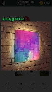 В помещении на стене повешен цветной квадрат и освещен изнутри