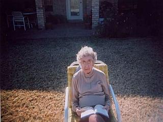 An elderly woman enjoying reading a book outdoors