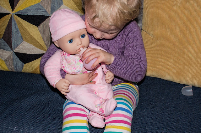 A toddler giving Baby Annabell her bottle