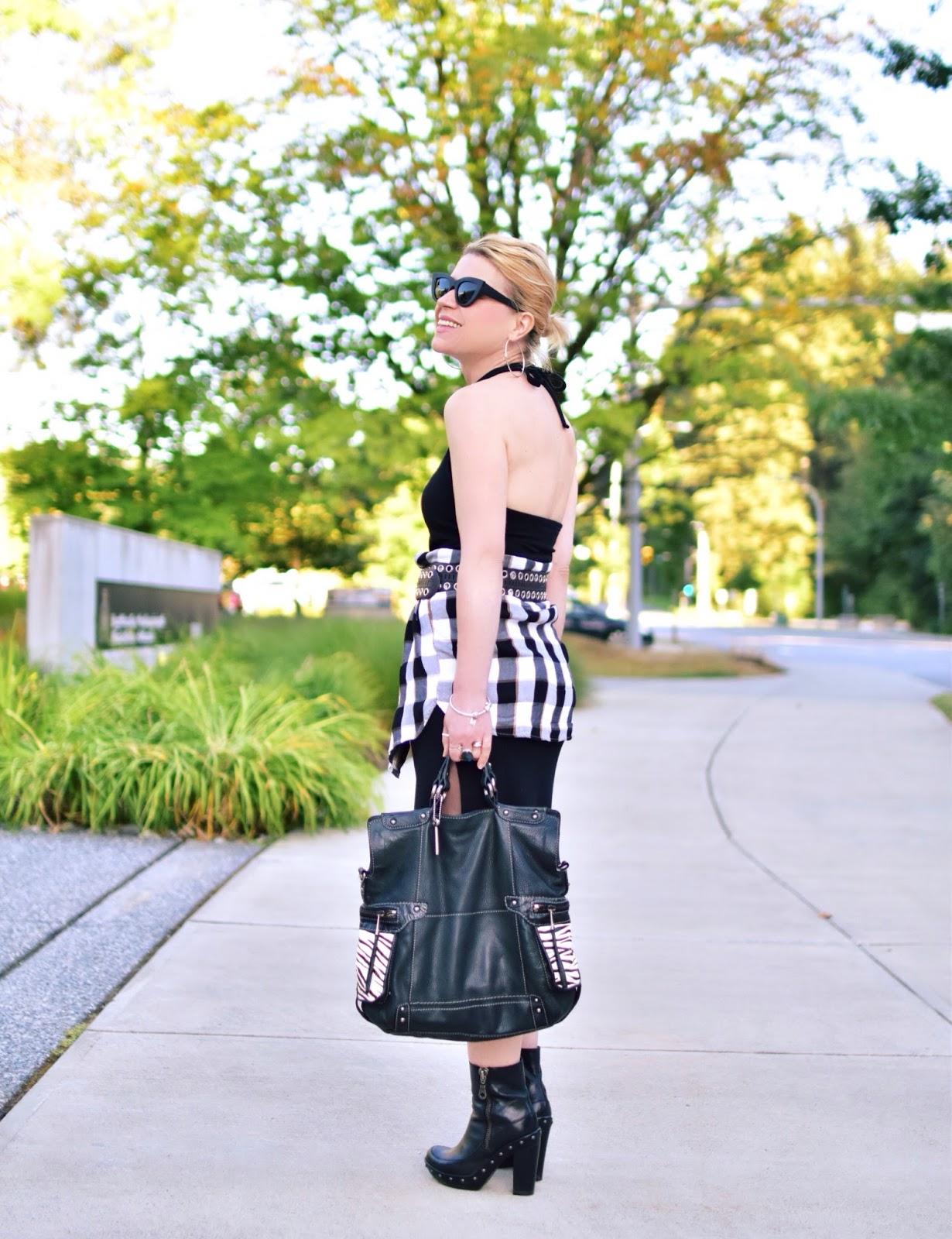 Monika Faulkner styles a halter dress with a waist-wrapped plaid shirt, grommet belt, platform booties, and cat-eye sunglasses