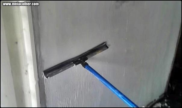 alisando massa corrida na parede com rodo