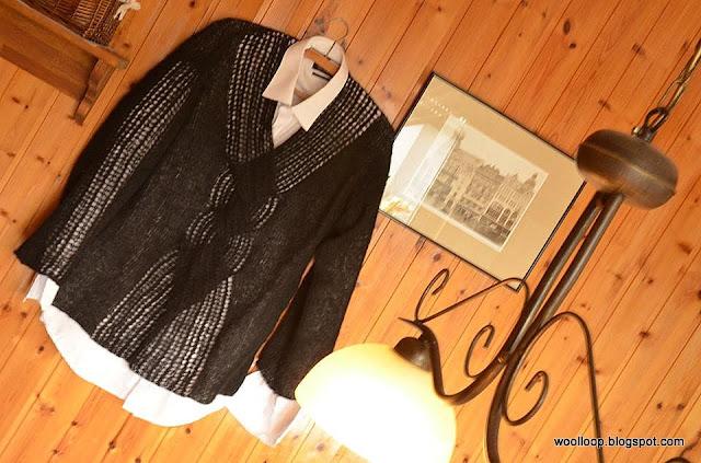 Czarny, ażurowy sweter dziergany na tle drewnianej ściany, obok zdjęć miasta w sepii.