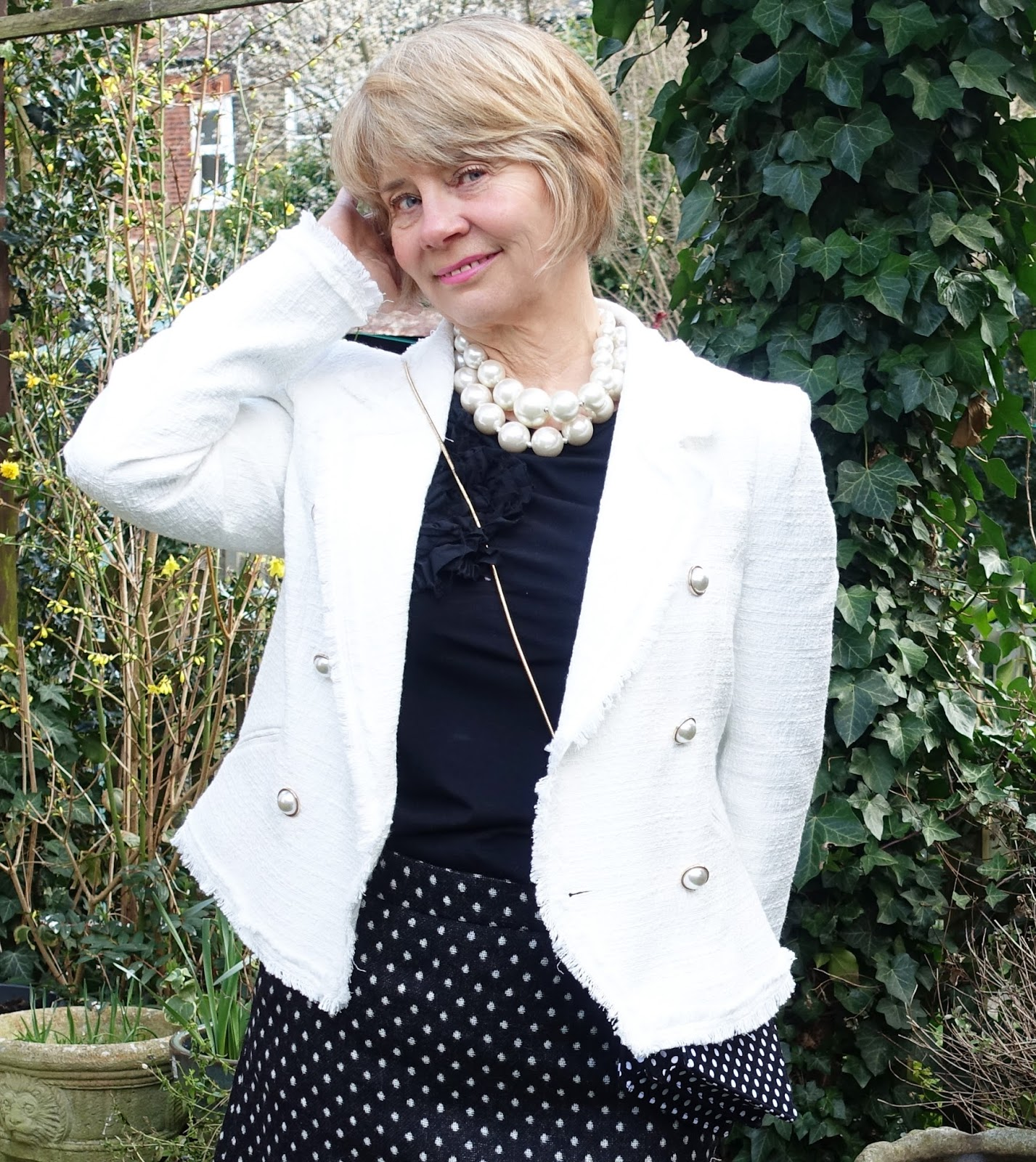 Image showing a woman in a white boucle jacket with a polka dot above the knee skirt and pearl necklaces