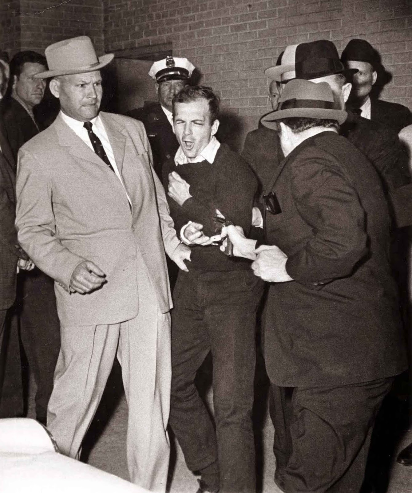 Ruby about to shoot Oswald who is being escorted by Dallas police. Det. Jim Leavelle is wearing the tan suit. Det. L.C. Graves is wearing the dark suit.