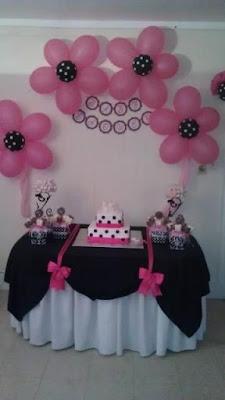Decor masa botez tematic Minnie Mouse cu baloane aranjate in forma de floare, culori roz si negru