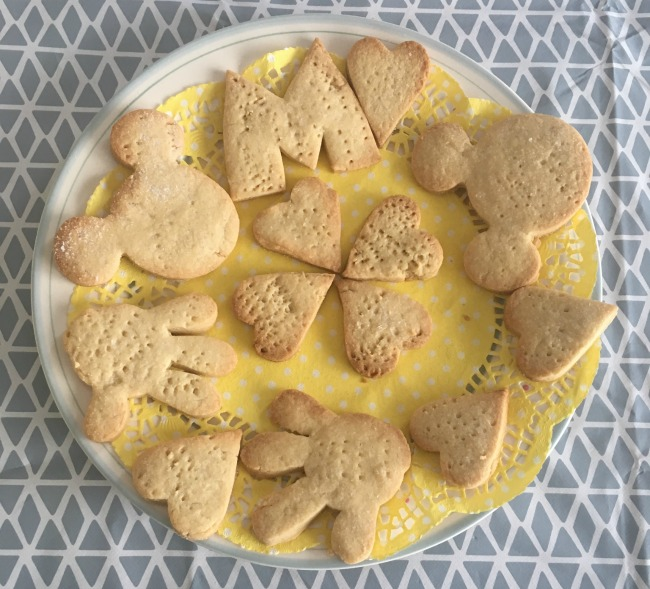 cooked-cookies-on-yellow-doilley-shapes-are-Mickey-Mouse-head-hands-and-letter-M-and-hearts