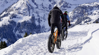 A picture of cycling in the snow in winter.