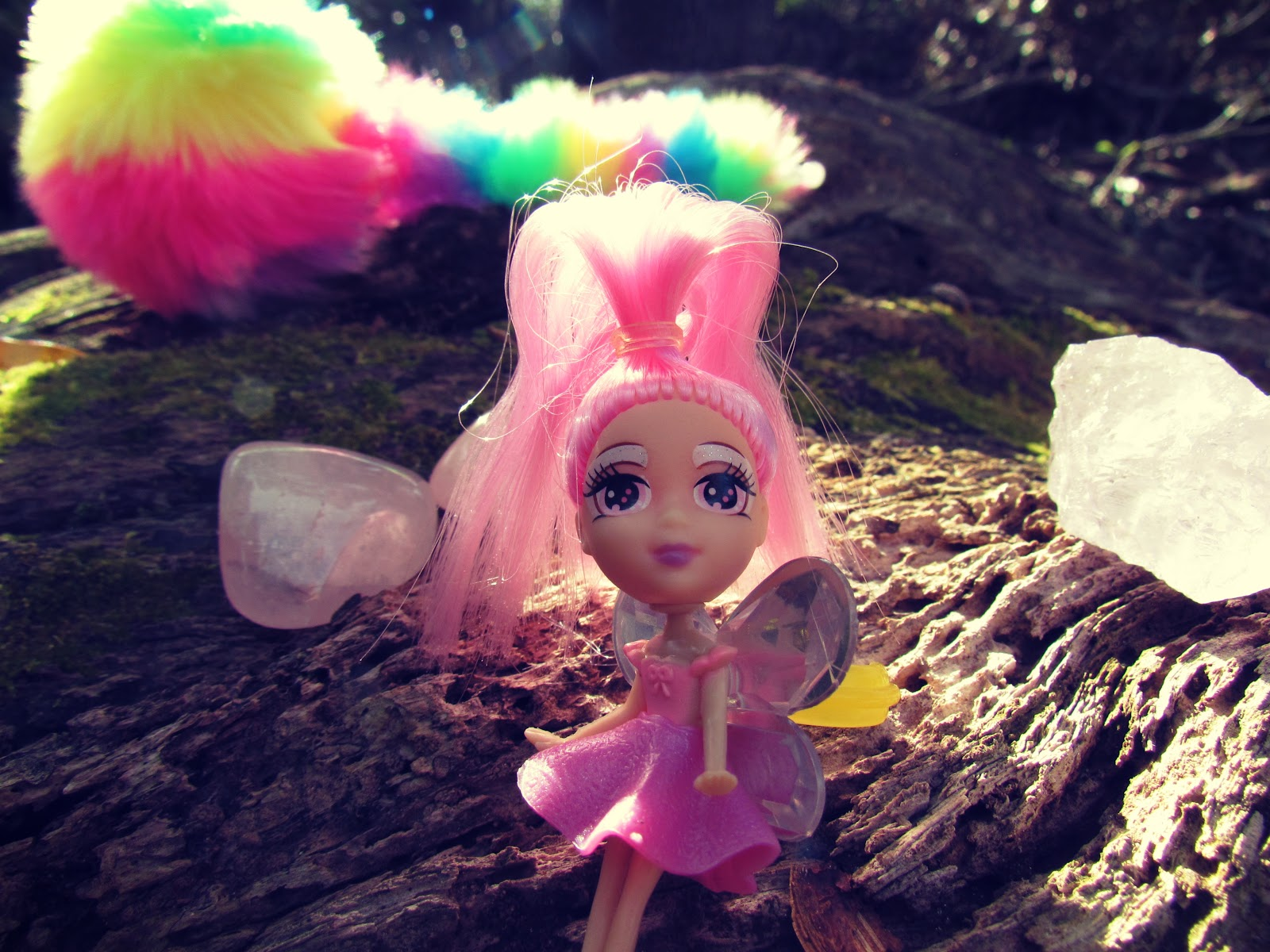 A Pink Fairy Doll Ring Dollar Store Find Sitting on a Tree Stump With Fuzzy Novelty Pens in Nature