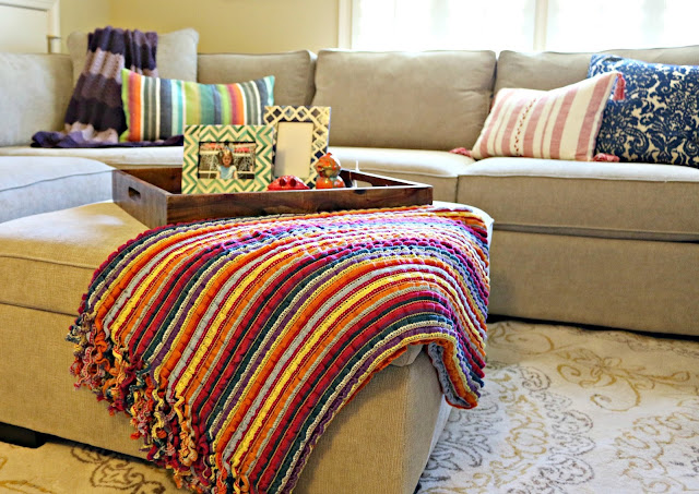 Family room sectional with global bohemian rug, pillows, and accessories