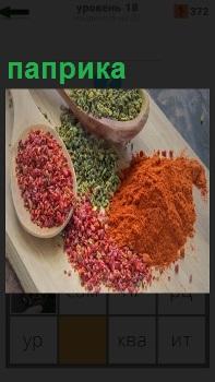 На разделочной доске и в ложках лежит цветная паприка для приготовления в пищу