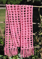 A photograph of a pink lacy scarf hanging over a bamboo trellis with a garden backdrop. The scarf is made using a tricot technique and has straight fringing on each end.