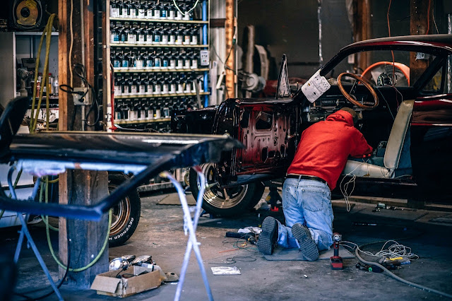 Man working on his car in a garage