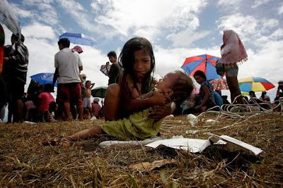 a young girl cuddling her baby sister and crying while waiting for a plane to get them out of Tacloban