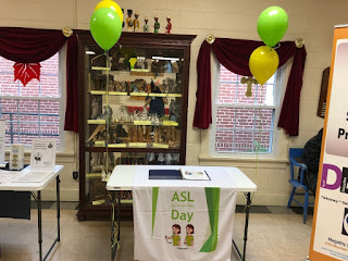 "Table with banner ""ASL day"" and papers showing basic ASL"