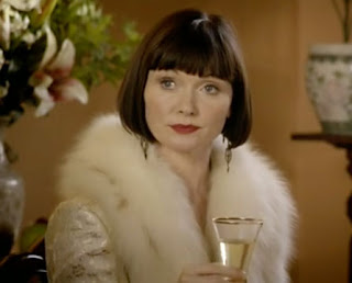 Phryne Fisher in a white lame coat with white fur collar