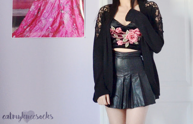 Black velvet rose applique floral embroidered bralette/cropped cami top from SheIn, worn with a faux leather pleated tennis skirt and knit cardigan.