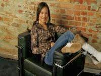 Веселая молодая женщина сидит за каменной стеной в удобном мягком кресле.