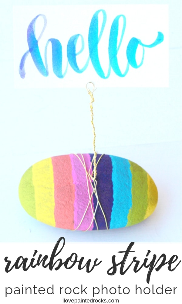 How to make a DIY photo holder stand with wire and a rock. Perfect for tables as a centerpiece, to hold polaroids, photos, or as name tags at a wedding. I love the look of the rainbow striped rock, too. It's such a cute picture frame idea. This would make a great mother's day gift! #ilovepaintedrocks #rockpainting #paintedrock #rainbow #giftideas #mothersday #DIYgifts #stonepainting #paintedstones #eastercrafts