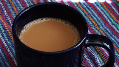 Hot cup of coffee with cream on a colorful background