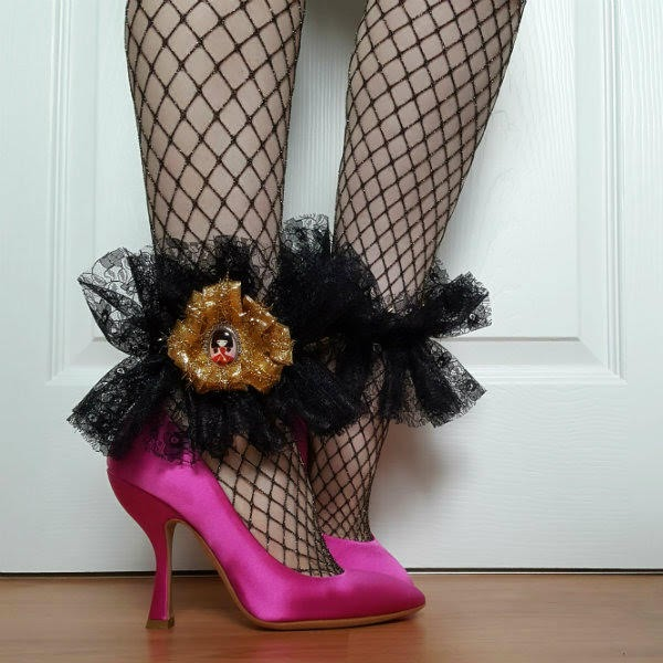 side angle of legs in fishnet tights wearing pink satin shoes with black lace handmade ankle cuffs