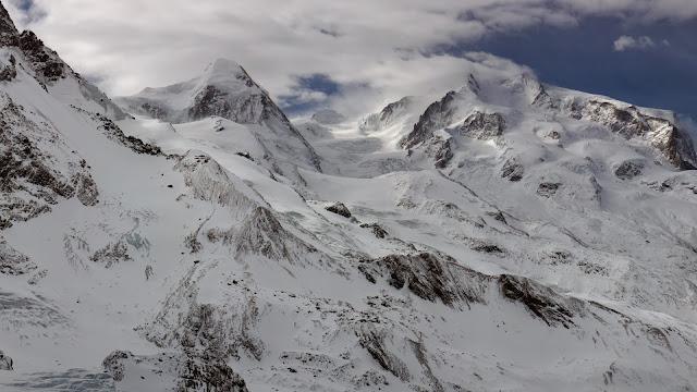 Bergen met sneeuw in de wolken