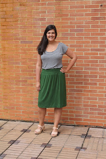 Modeling a DIY self-drafted basil green rayon knit skirt and a striped top in front of a brick wall..