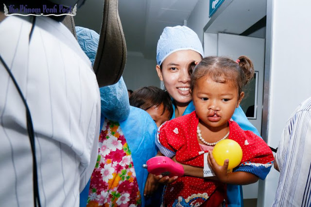 A member of Operation Smile carries a child with a cleft lip through Phnom Penh's Preah Kosmak Hospital in 2014. Heng Chivoan