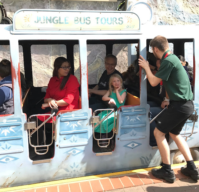 "Side view of a mini bus with open sides and the words ""Jungle bus tours"" on it"