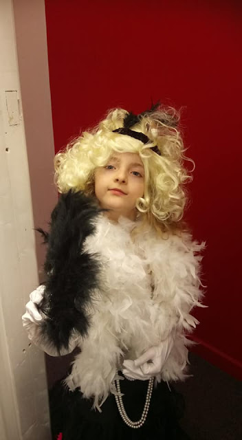 Molly in a blonde wig and dressed up with feathers and pearls!