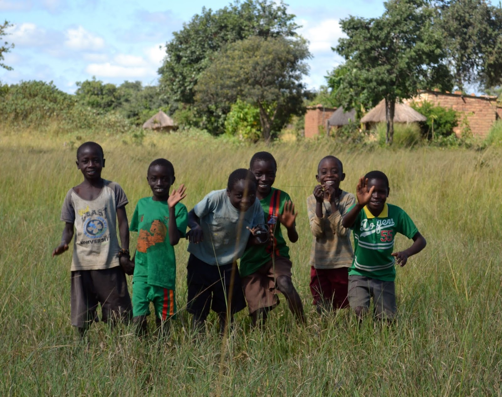 a group of boys waving in zambia