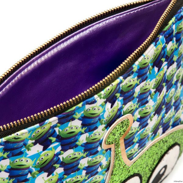 close up of alien clutch bag slightly opened with purple lining and zip top