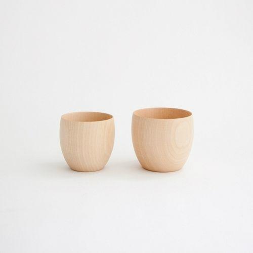 Zwei Tassen aus hellem Holz stehen nebeneinander vor einer weißen Wand