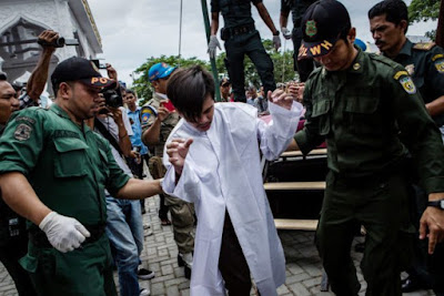 Indonesian man escorted after public caning for having gay sex.