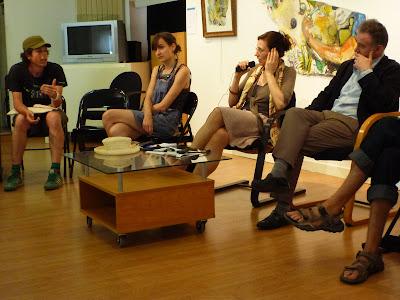 Diskussionssituation in einem Kulturhaus mit Diskutanten, Dolmetscherin, Festivalleiter