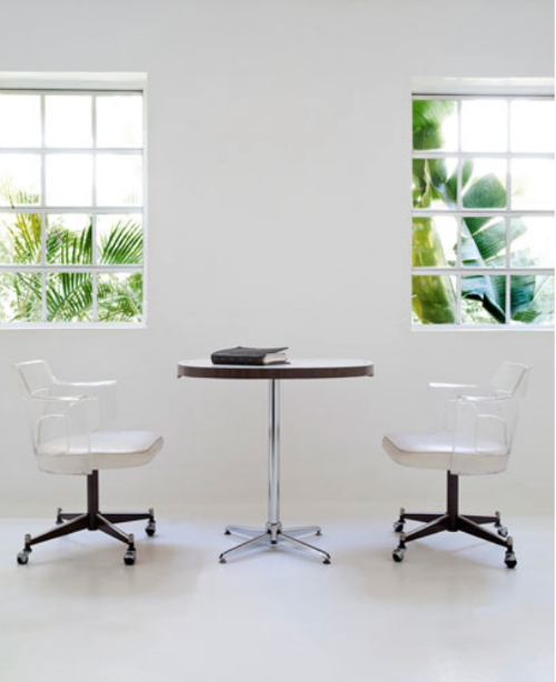Große Fensterfront, vor der ein Tisch und zwei Stühle stehen - alles in Weiß getaucht.