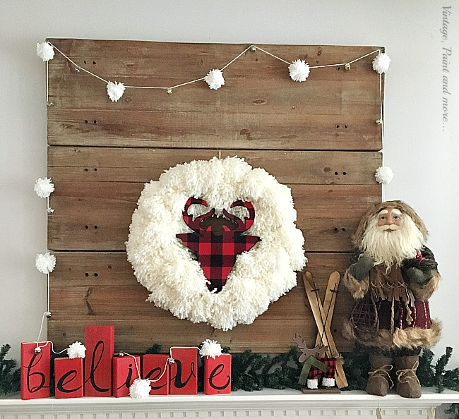 Vintage, Paint and more... a rustic Christmas mantel made with diy yarn wreath with a buffalo plaid wood deer head, a wood BELIEVE sign, and diy pom-pom garland