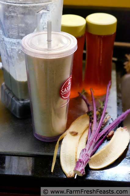 a side view of a banana, peanut butter, and date smoothie with curly kale